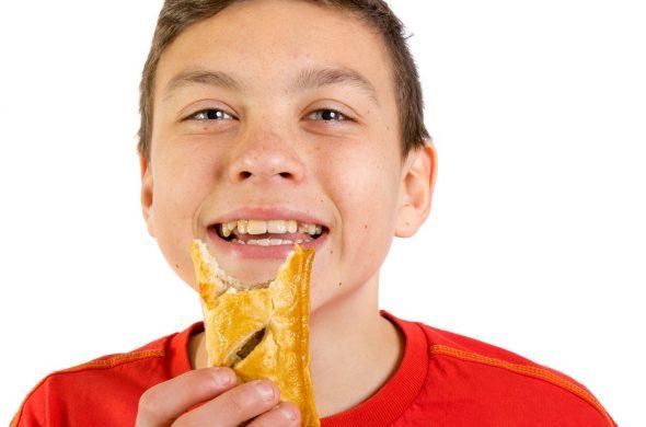 イギリスの名物料理ミートパイを食べる少年