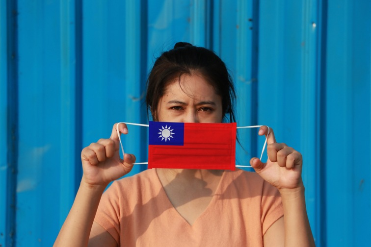 台湾の国旗の柄マスクをもったアジア女性