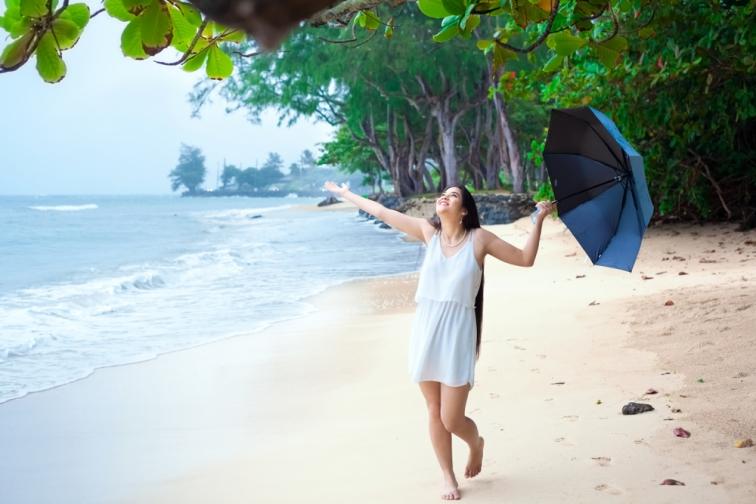 タイのビーチで傘を持って笑っている女性