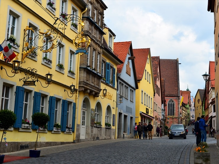 ミニチュアのような建物に囲まれた街の通り。古くからこの地方で盛んな鍛冶技術が活かされた看板も必見だ