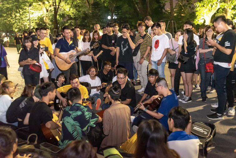 ホアンキエム湖周辺で大勢で集まり合唱する若者たち