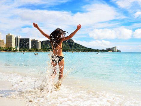 Waikiki beach fun - happy woman on Hawaii vacation