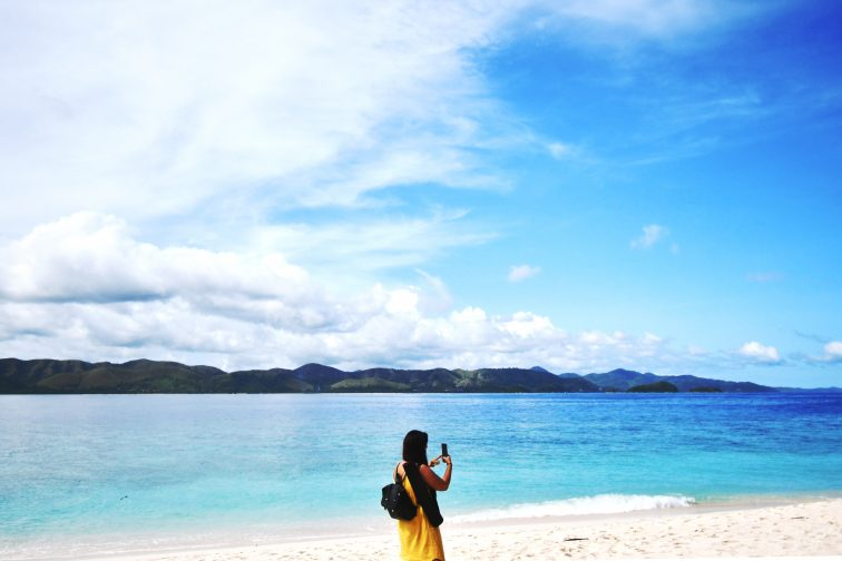 a girl taking pictures on the beach