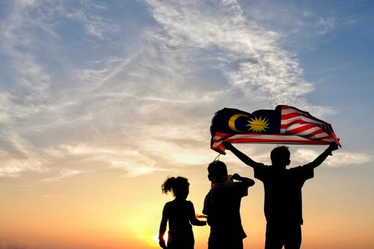 マレーシアの国旗を掲げる子供たちのシルエット