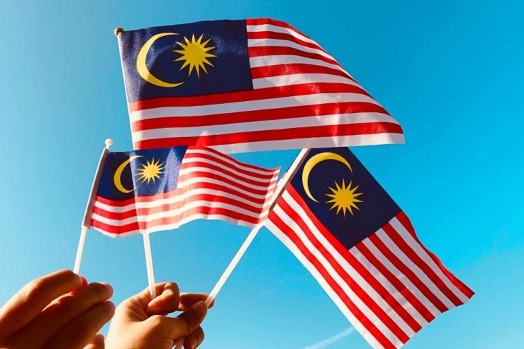 マレーシアの国旗を手で持っている