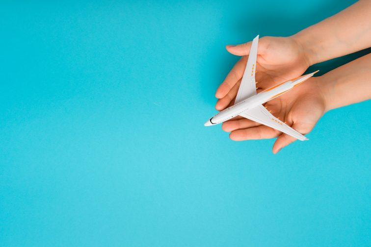 Hand carefully holding model plane. Airplane on blue color backg
