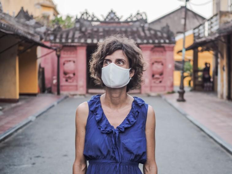 ベトナム観光地ホイアンでマスクを付けて立っている欧米人女性