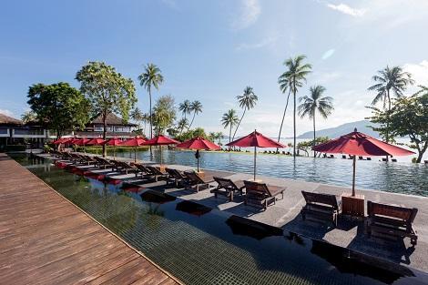 ヴィジットリゾートのプールとプールサイドに並ぶパラソルとビーチチェア